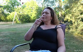 Smoking mature lady finger fucks her cunt in the backyard