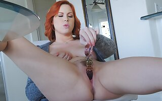 Hot redhead slides her glass toy deep down the pussy